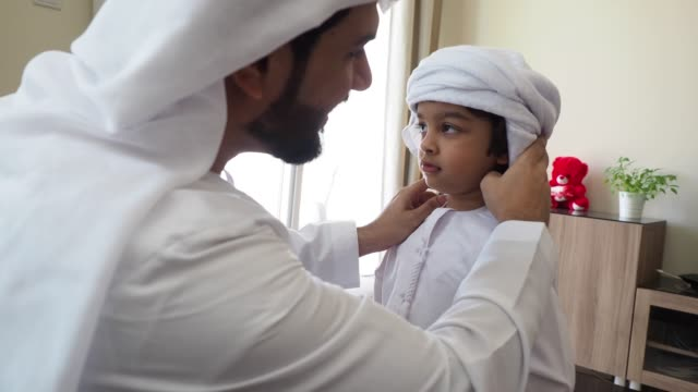 arab man fixing keffiyeh to his son - modern stock videos & royalty-free footage