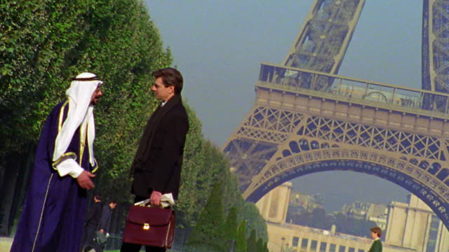 CANTED Arab man in robes + headdress talking to businessman with briefcase in front of Eiffel Tower