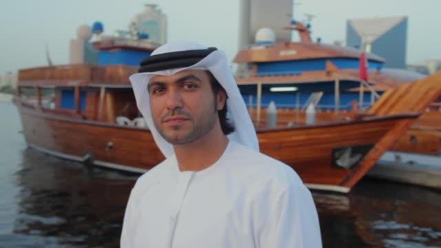 ms pan zi cu arab man in traditional dish dash at dubai creek / dubai, united arab emirates - middle eastern culture stock videos & royalty-free footage