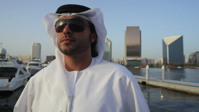 cu ms tu arab man in traditional dish dash at dubai creek, skyline in background / dubai, united arab emirates - dish dash stock videos & royalty-free footage
