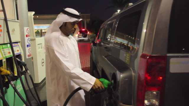 MS ZI Arab man in traditional dish dash filling car with petrol at gas station / Dubai, United Arab Emirates