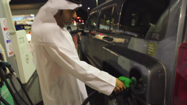 MS ZO Arab man in traditional dish dash filling car with petrol at gas station / Dubai, United Arab Emirates