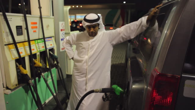 MS ZO ZI Arab man in traditional dish dash filling car with petrol at gas station / Dubai, United Arab Emirates