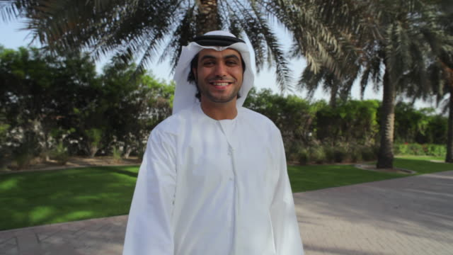 MS POV Arab man in traditional dish dash shaking hands, smiling / Dubai, United Arab Emirates