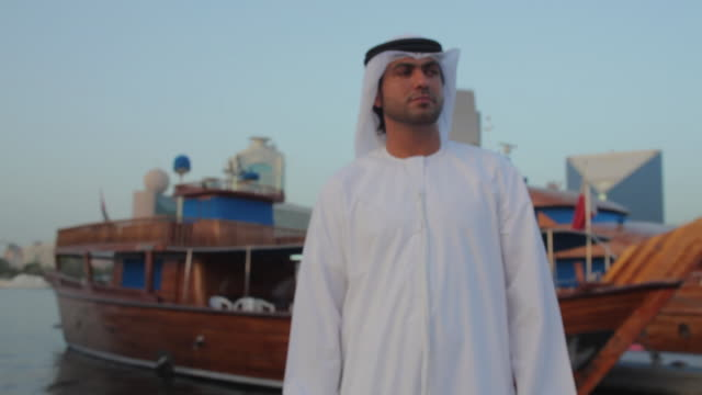 CU TU ZI Arab man in traditional dish dash standing at Dubai Creek / Dubai, United Arab Emirates