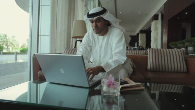 ws arab man in traditional dish dash using laptop in hotel lobby / dubai, united arab emirates - dish dash stock videos & royalty-free footage