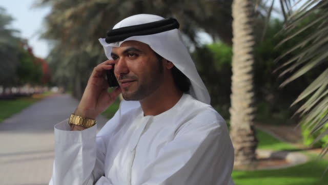 cu arab man in traditional dish dash using mobile phone / dubai, united arab emirates - men stock videos & royalty-free footage