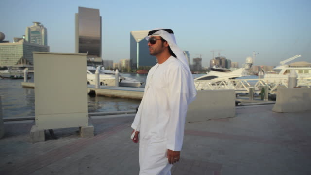 MS TS Arab man in traditional dish dash walking along Dubai Creek, skyline in background / Dubai, United Arab Emirates