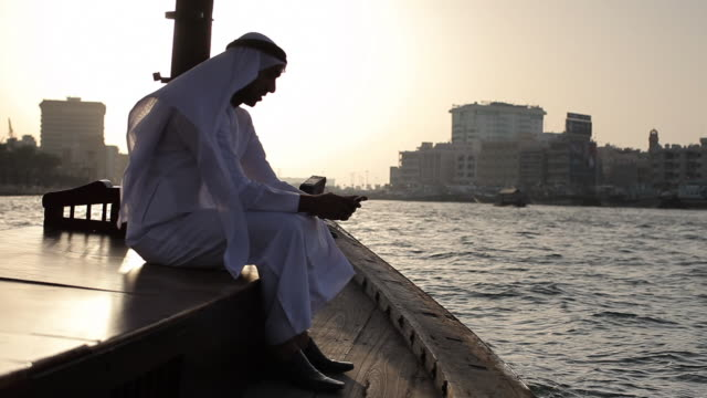 ws arab man in traditional dress on ferry boat in dubai creek/dubai/uae - golfstaaten stock-videos und b-roll-filmmaterial