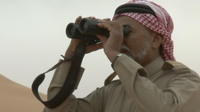 cu arab man looking through his binoculars / najran city, najran, saudi arabia  - saudi arabia stock videos & royalty-free footage