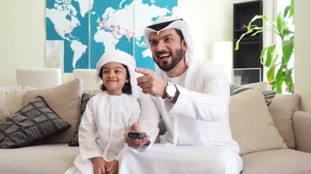 arab man looking tv at home with his son - television industry stock videos & royalty-free footage