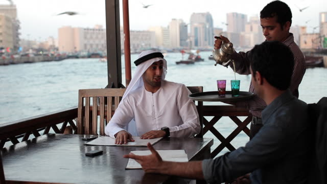 CU MS Arab man serving tea to two friends in outdoor restaurant/Dubai/UAE