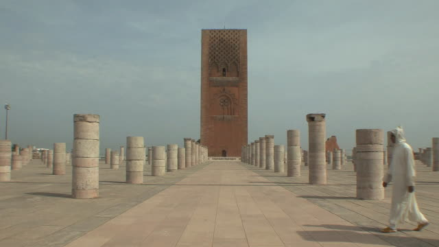 ws arab man wearing jellaba walking across yascoub al mansour esplanade, rabat, morocco - minareto video stock e b–roll