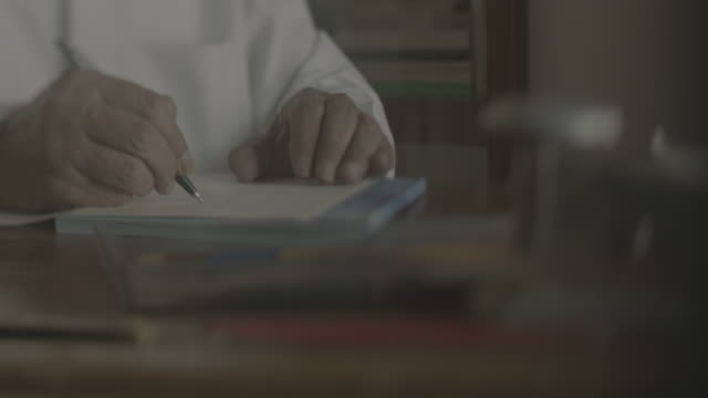 arab man writing a letter tracking shot on the hands of an old bahraini arab man writing a letter in arabic on a vintage desk - pen stock videos & royalty-free footage