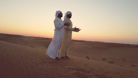 vidéos et rushes de les hommes arabes priant ensemble dans le désert - prier