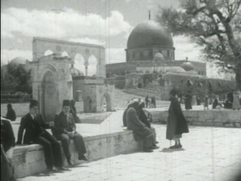 jerusalem palestine *arab men standing sitting on short wall w/ others walking plaza bg landmark 'the dome of the rock' islamic shrine on top of... - 1938 stock-videos und b-roll-filmmaterial