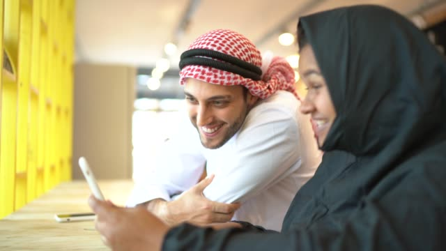 arab middle east couple doing a video call on mobile phone at coffee shop - middle eastern ethnicity stock videos & royalty-free footage