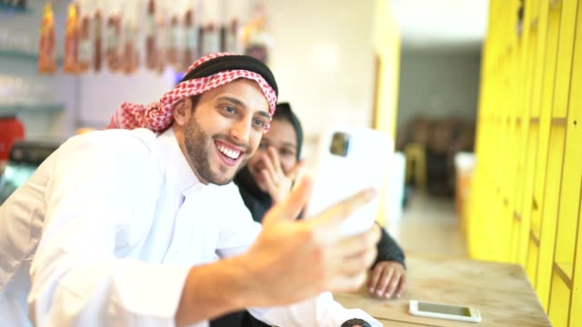 arab middle east couple doing a video call on mobile phone at coffee shop - greeting stock videos & royalty-free footage