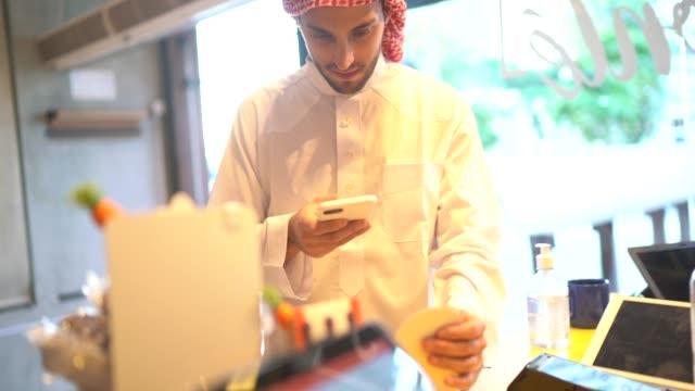 アラブ中東の男性がコンビニエンスストアでモバイル決済を行っている - 注文する点の映像素材/bロール