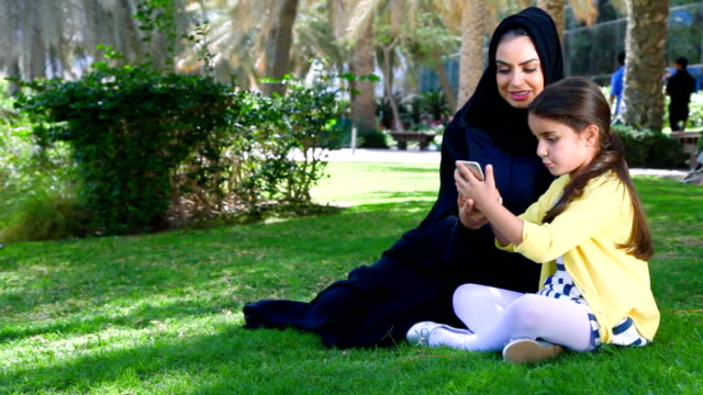 Arab mother and daughter enjoying with smartphone at park