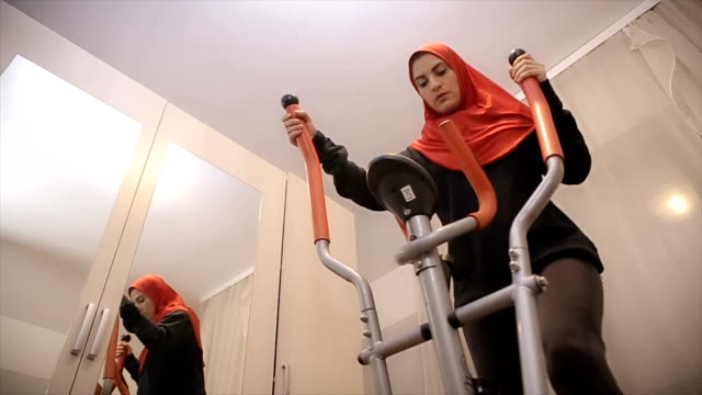 arab woman is training at a sports exercise machine - modest clothing stock videos & royalty-free footage