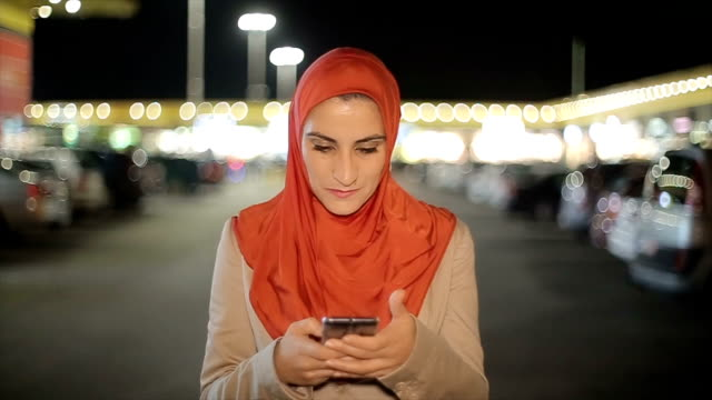 Arab woman using mobile phone on the street at night