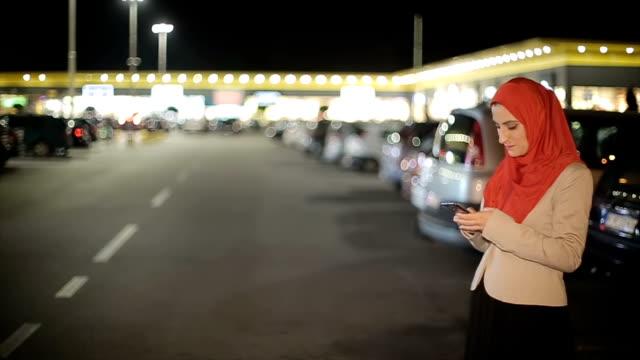 Arabische Frau mit Handy auf der Straße in der Nacht