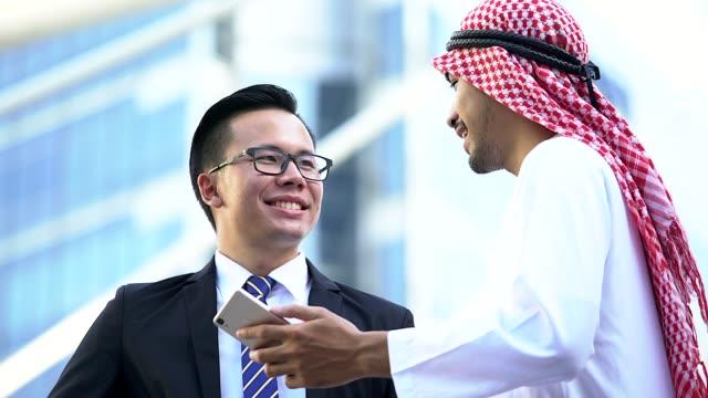vídeos de stock, filmes e b-roll de discussão de empresários árabe e chinês em uma reunião de negócios. fundo de cidade moderna. cooperação no exterior e negócios internacionais. - países do golfo