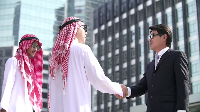 アラビア語と中国語のビジネスマンのハンド シェーク。近代的な都市の背景。国際ビジネスと海外協力。 - コミュニケーション点の映像素材/bロール