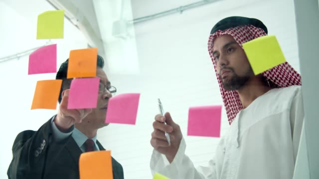 arabic businessman wearing islamic clothes sharing business strategy plan idea - middle eastern ethnicity stock videos & royalty-free footage