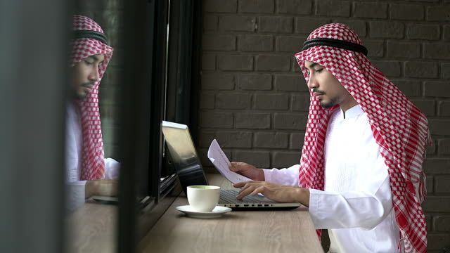 Arabic businessman wearing islamic clothes working with notebook in the coffee shop.