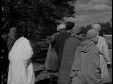 arabic men crowding italian agent ws tunisian radio stations on hill slope int ms arabs listening to radio ext vs group of arabs listening to radio... - radio broadcasting stock videos & royalty-free footage