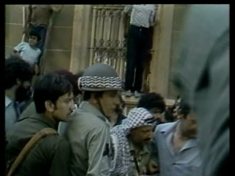 WestBeirut EXT Yasser Arafat kisses wellwishers INT Arafat and Walid Jumblatt seated giving interviews Arafat along through crowd to car as rice is...