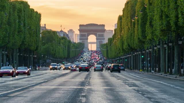 arc de triomphe and traffic at avenue des champs-elysees in paris - 4k time lapse - arc de triomphe paris stock videos & royalty-free footage