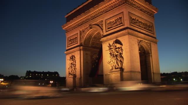 vidéos et rushes de t/l, ws, arc de triomphe illuminated at night, traffic on street in foreground, place charles de gaulle, paris, france - arc élément architectural