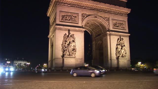 vidéos et rushes de ws, arc de triomphe illuminated at night, traffic on street in foreground, place charles de gaulle, paris, france - arc élément architectural