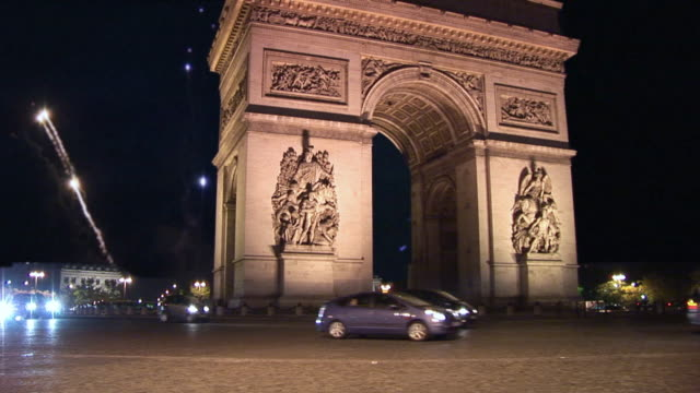 vidéos et rushes de ws, arc de triomphe illuminated at night with fireworks in background, place charles de gaulle, paris, france - arc de triomphe paris