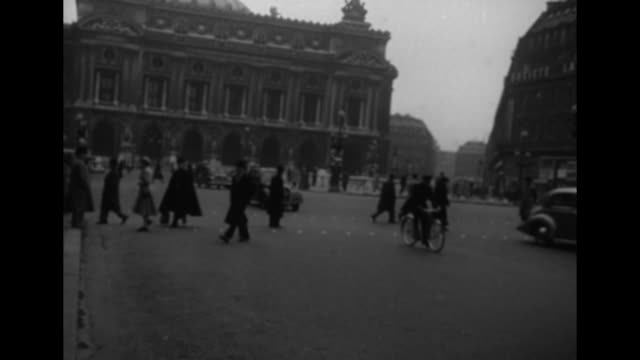 Arc de Triomphe / numerous people wave from atop a horsedrawn omnibus / pedestrians on street with light traffic / empty rail yard / couple at van /...