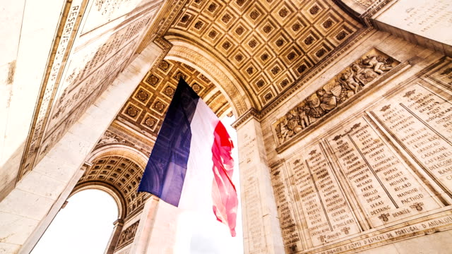 arc de triomphe with french flag - triumphal arch stock videos & royalty-free footage
