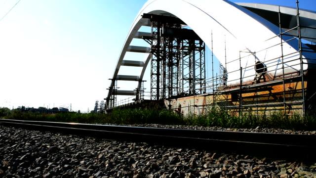 arch bridge construction near railway lane and building bars - arch bridge stock videos and b-roll footage