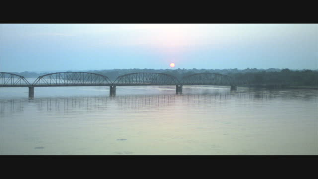 low aerial, arch bridge crossing wide river at sunrise - anamorphic stock videos and b-roll footage