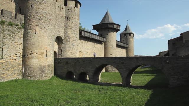 vídeos de stock, filmes e b-roll de ws arch bridge leading to entrance of carcassonne / languedoc-roussillon, france - carcassonne