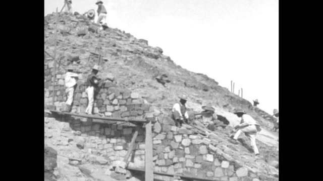 ws archaeological dig workers on stepped slope of ancient ruin possibly in mesoamerica / workers hammer at large stones / workers on another slope /... - arte dell'antichità video stock e b–roll