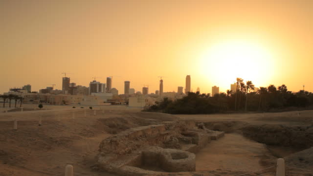 archaeological site at sunset with the skyscrapers of manama in the background. - contrasts stock videos & royalty-free footage