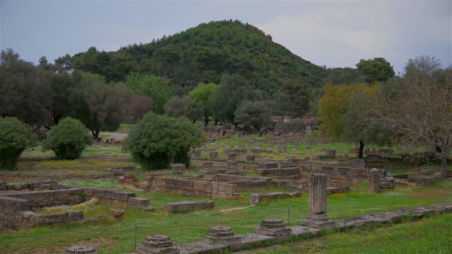 vídeos y material grabado en eventos de stock de sitio arqueológico de la antigua olimpia, ruinas de leonidaion en olympia y árbol de judas ( cercis siliquastrum ), peloponnes, grecia - judas