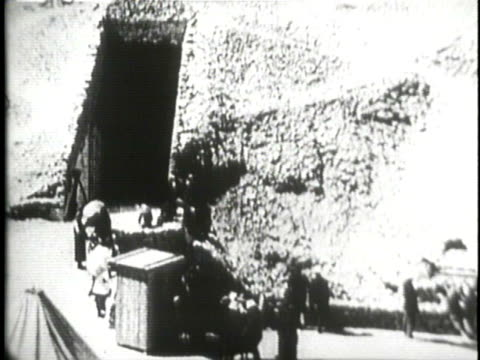 Archaeologist work near the Sphinx and the pyramids as Arab men help remove a large wooden crate from a tomb