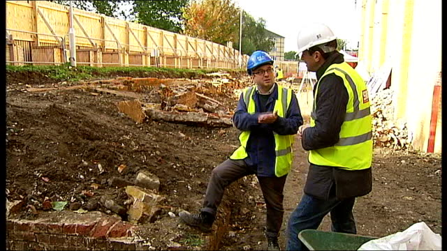 500 skeletons found in crypts at construction site of new leisure centre england london elephant and castle ext modern building seen beyond trees... - gartengerät stock-videos und b-roll-filmmaterial