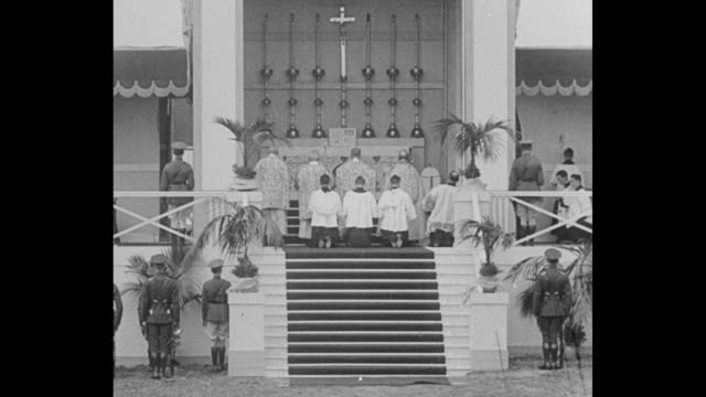 archbishop edward byrne saying mass on outdoor altar in phoenix park with other priests and altar boys / shot of huge crowd in phoenix park attending... - altar stock videos & royalty-free footage
