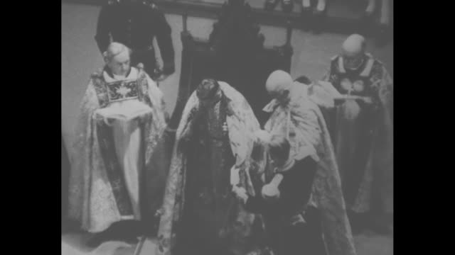 archbishop of canterbury hands king george vi the sword of state as he sits in king edward's chair / king stands and puts sword in scabbard / dean of... - archbishop of canterbury stock videos & royalty-free footage