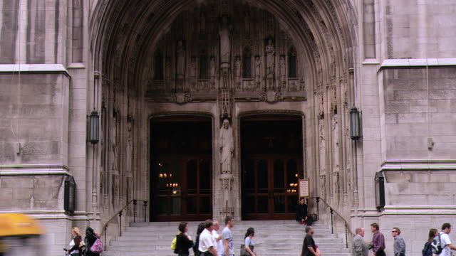 zo arched entrance and doors of st. patrick's cathedral, facade with flying american and roman catholic flags, and pedestrians and traffic / new york city, new york, united states - st. patrick's cathedral manhattan stock videos and b-roll footage